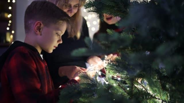mother and kids putting christmas lights on christmas tree - imgorthand stock videos & royalty-free footage
