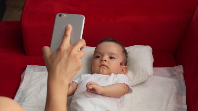 mutter und kleines baby im gespräch mit familie über handy - little girl webcam stock-videos und b-roll-filmmaterial