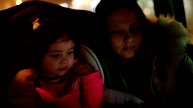 mother and little daughter in car at night - belt stock videos & royalty-free footage
