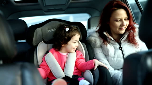 mother and little daughter on back seat in car