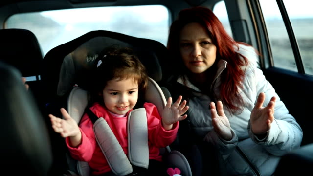 母と車で後部座席に小さな娘 - 車内点の映像素材/bロール