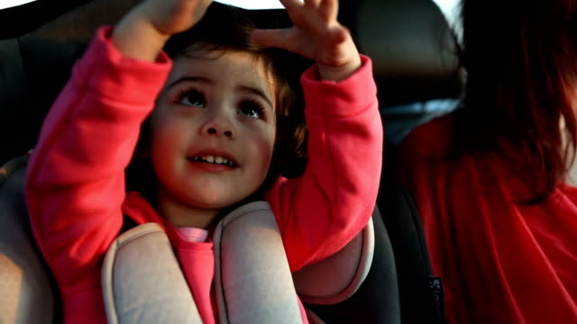 mother and little daughter on back seat in car - cintura di sicurezza video stock e b–roll