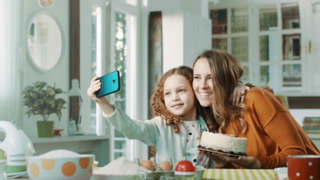 mutter und mädchen nehmen selfie mit geburtstagstorte - kuchen und süßwaren stock-videos und b-roll-filmmaterial