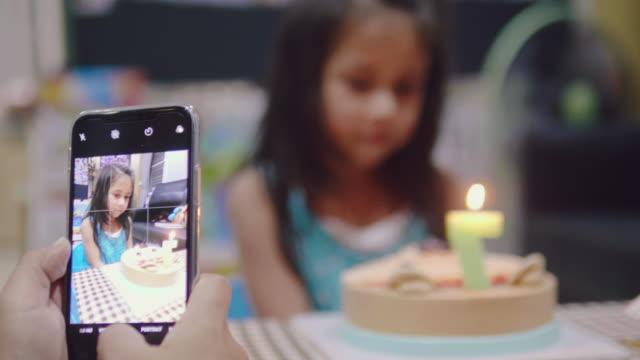 vídeos de stock, filmes e b-roll de mãe e filha falando de foto no bolo de aniversário - data especial