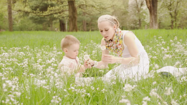 Mother and little son blowing dandelions in grass