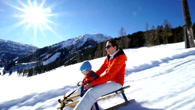 mother and little son tobogganing