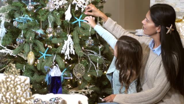 vídeos de stock, filmes e b-roll de mãe e filha de raça mista, com tema praia natal - enfeitar a árvore de natal