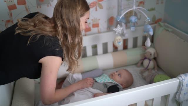 stockvideo's en b-roll-footage met moeder en pasgeboren zoon die van de babyjongen pret in babykribben hebben - wieg