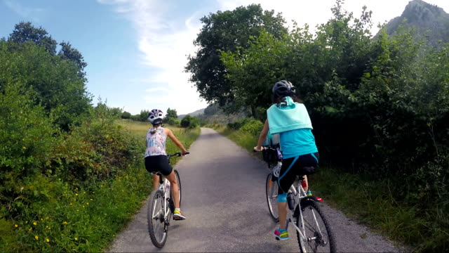 mother and pre-teen daughter riding on bikes on a thin road in nature. - following moving activity stock videos and b-roll footage