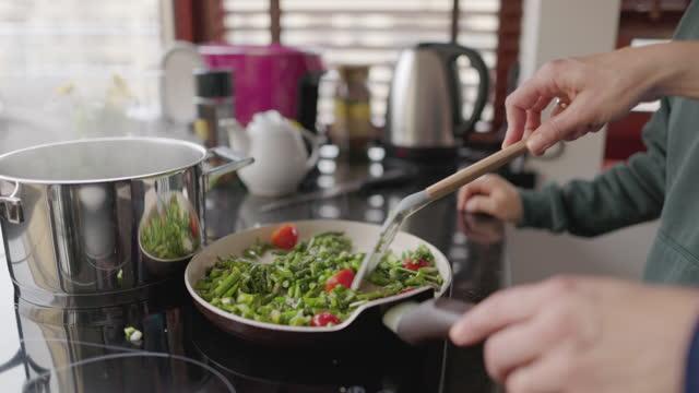 vidéos et rushes de mère et fils préparent des asperges sautées avec de l'ail et des tomates cerises - son
