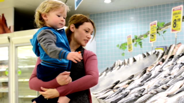 mother and son at fish market - fish market stock videos and b-roll footage