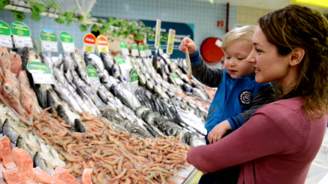 mother and son at fish market - fish market stock videos & royalty-free footage