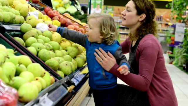 vídeos y material grabado en eventos de stock de madre e hijo en la tienda de comestibles - pera