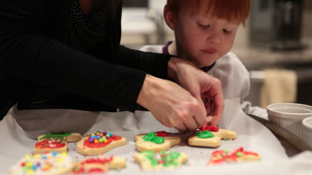 mother and son baking and decorating cookies - baking stock videos and b-roll footage