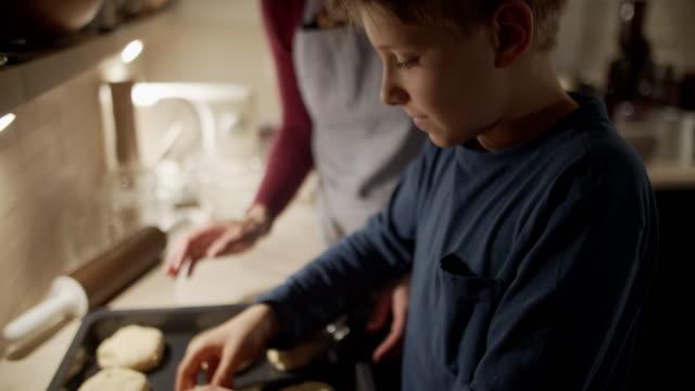 vídeos de stock e filmes b-roll de mother and son baking bread buns - pão