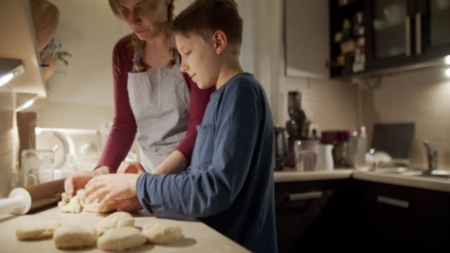 mother and son baking bread buns - tilt down stock videos & royalty-free footage