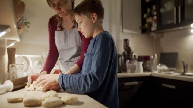 mor och son baka brödbullar - enbarnsfamilj bildbanksvideor och videomaterial från bakom kulisserna