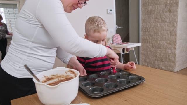 母と息子が一緒にマフィンを焼く - マフィン点の映像素材/bロール