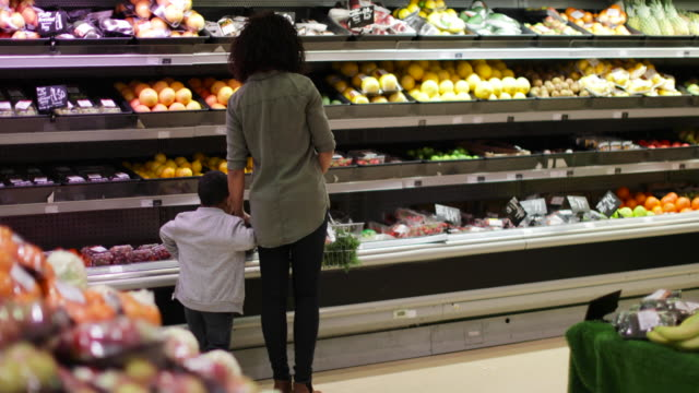 vidéos et rushes de mother and son buying fruit and vegetables in grocery store - plan en travelling