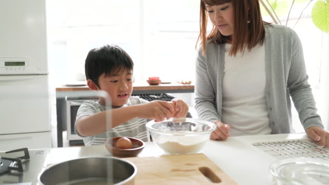 Mother and son cooking together in the kitchen