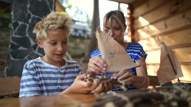 mother and son crafting boats - patio stock videos & royalty-free footage