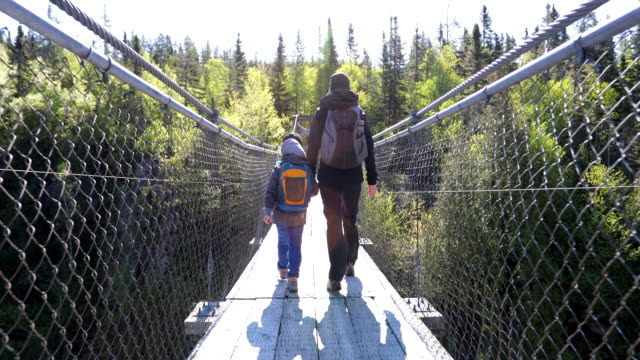 mother and son crossing a suspension bridge in aiguebelle national park - suspension bridge stock videos & royalty-free footage