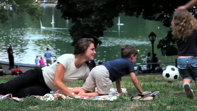 stockvideo's en b-roll-footage met ms mother and son  daughter  throw soccer ball into air / new york, new york, united states   - picknick