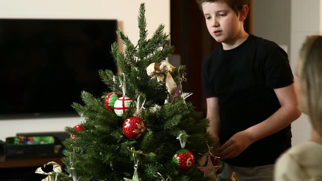 vídeos de stock e filmes b-roll de mother and son decorating christmas tree - arvore de natal