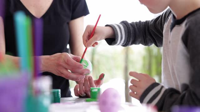 vídeos y material grabado en eventos de stock de madre e hijo decorando huevos de pascua con pintura en casa - son