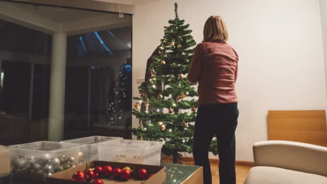mother and son decorating the christmas tree on christmas eve - time-lapse - christmas tree stock videos & royalty-free footage