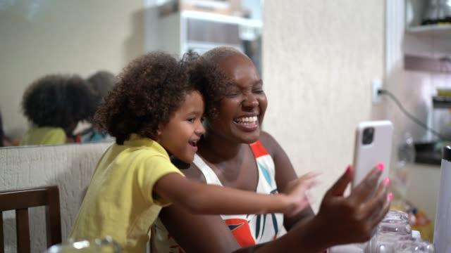 自宅で朝食時に携帯電話でビデオチャットをしている母と息子 - 人里離れた点の映像素材/bロール