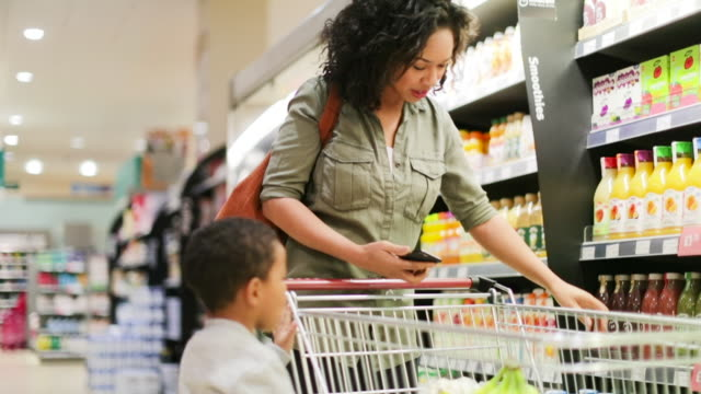 stockvideo's en b-roll-footage met mother and son doing weekly shop in grocery store - sap