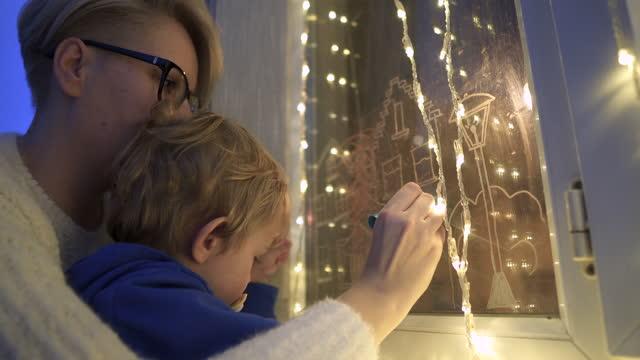 vidéos et rushes de la mère et le fils dessine la décoration de vacances de noël peinte sur le verre de fenêtre. - son