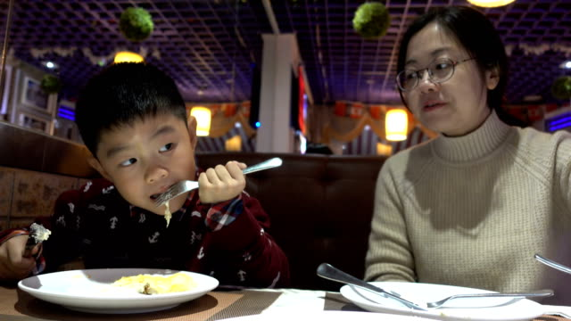 mother and son eating in western restaurant - french culture stock videos & royalty-free footage