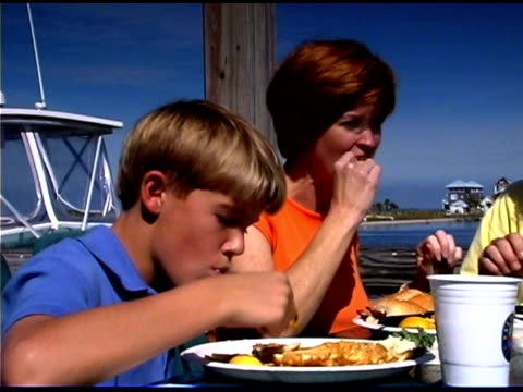 mother and son eating meal at outdoors restaurant near marina - see other clips from this shoot 1335 stock videos and b-roll footage
