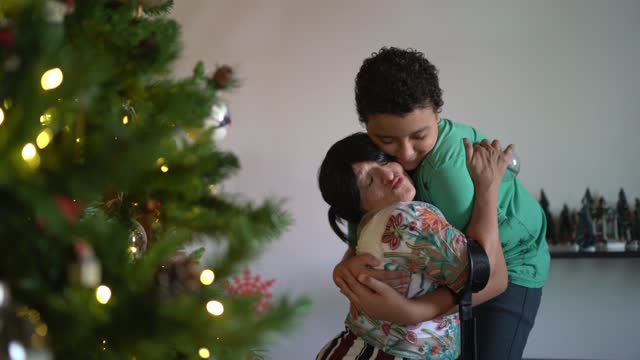 mother and son embracing while decorating christmas tree - nativity scene stock videos & royalty-free footage