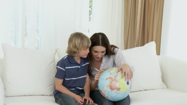 vídeos y material grabado en eventos de stock de ms mother and son examining globe, sitting on sofa / cape town, western cape, south africa - globo terráqueo para escritorio