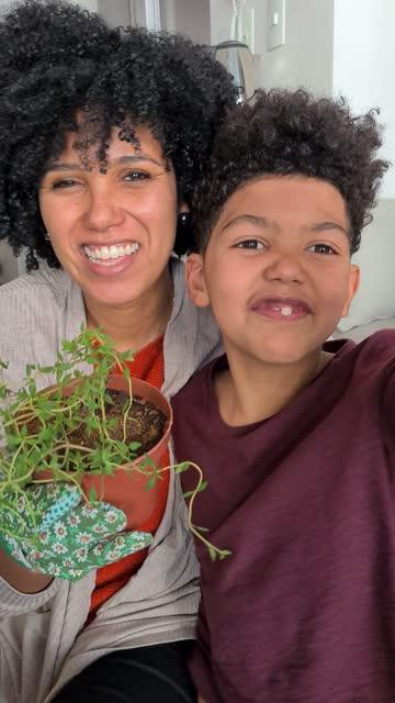 vídeos de stock, filmes e b-roll de mãe e filho jardinagem e compartilhá-lo na internet em casa - tomada em dispositivo móvel - jardinagem