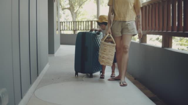 vidéos et rushes de invité de mère et de fils marchant dans la chambre d'hôtel - valise