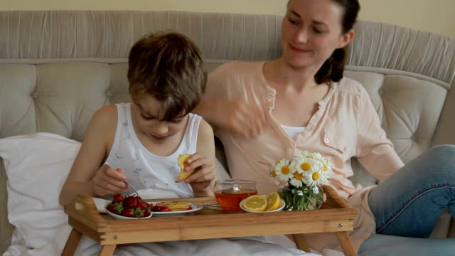 mother and son having breakfast in bed - 8 9 years stock videos and b-roll footage