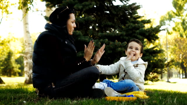 vidéos et rushes de mère et fils s'amuser dans le parc - son