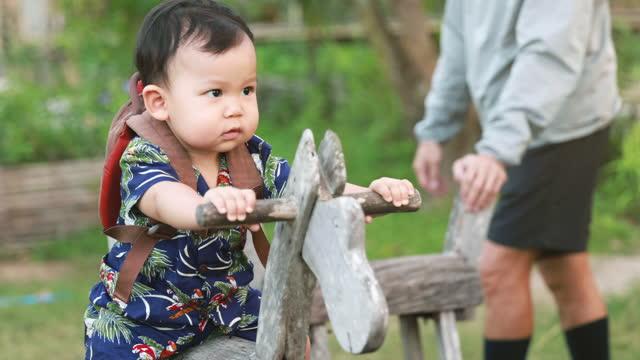 vídeos y material grabado en eventos de stock de madre e hijo divirtiéndose en la vieja tiovía de madera dar vueltas en el patio de recreo - son