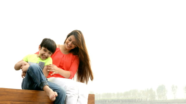 ms mother and son having fun while sitting on wooden jetty over lake / india - tickling stock videos & royalty-free footage