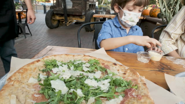 mother and son having pizza outdoors wearing protective face masks - protection stock videos & royalty-free footage