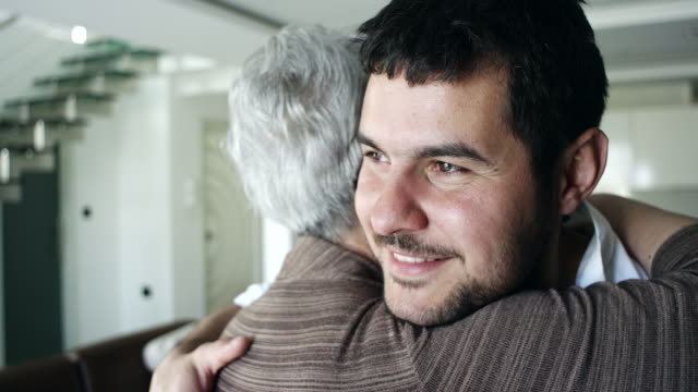 vídeos de stock e filmes b-roll de mother and son hugging in living room - filho