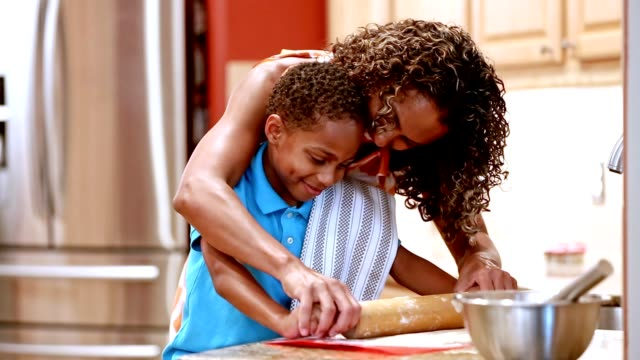 Mother and son in kitchen baking cookies.