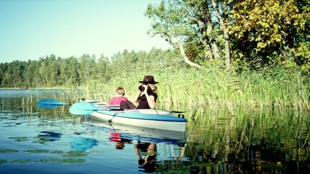 mother and son kayaking on a lake. mum making photos - femininity photos stock videos & royalty-free footage