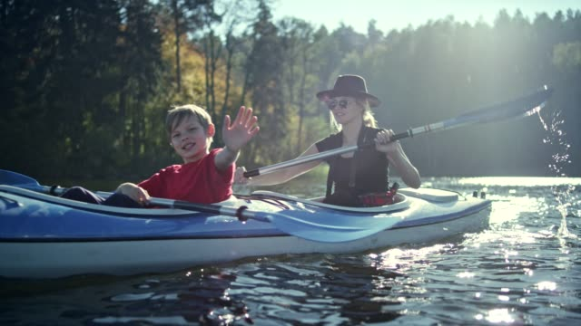 vídeos de stock e filmes b-roll de mother and son kayaking on a lake - kayaking