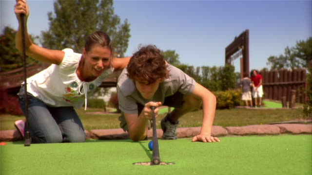 mother and son kneeling on mini golf course to measure putt / son putting golf ball into hole - golf club stock videos & royalty-free footage