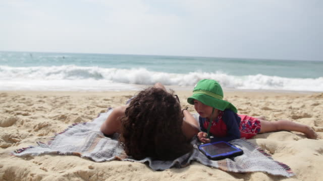 mother and son laying on beach looking at digital tablet in the south of france. - towel stock videos & royalty-free footage